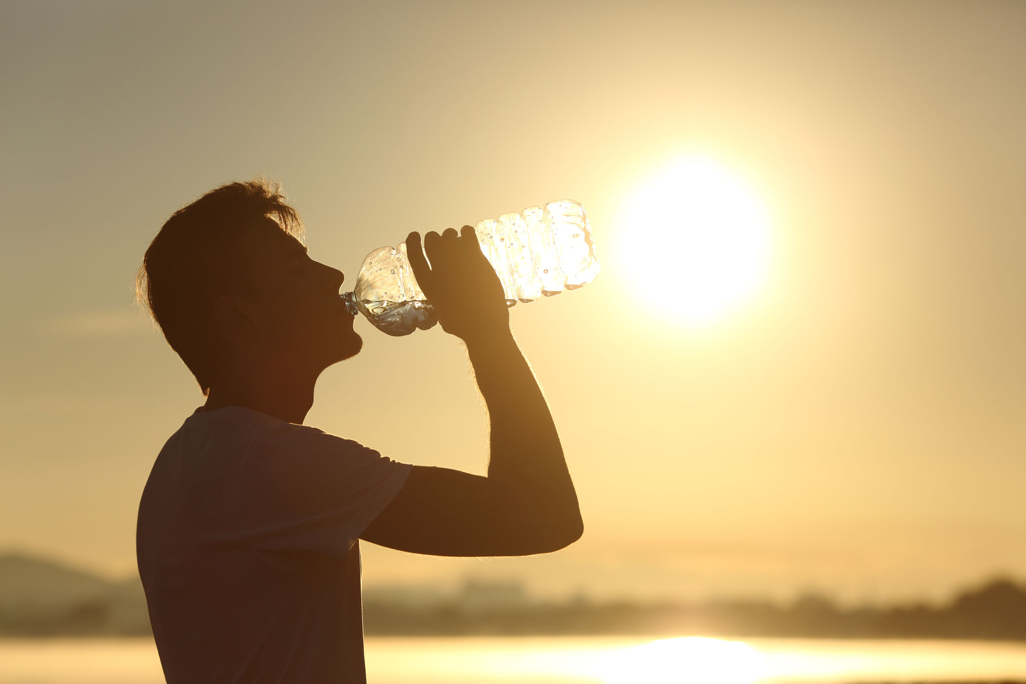 man drinking water in extreme heat