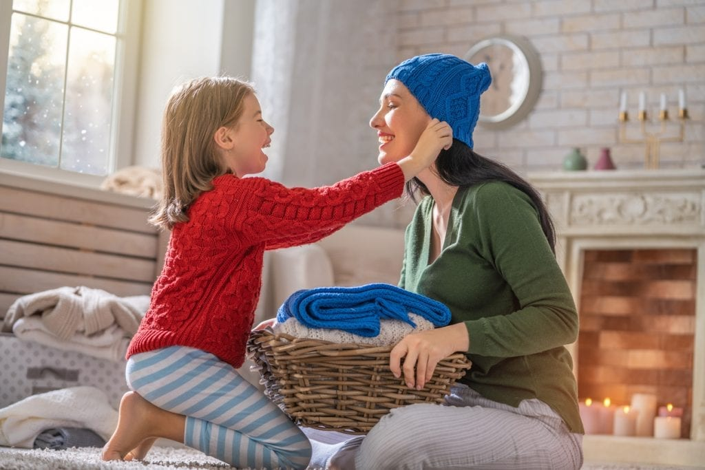 Winter portrait of happy loving family wearing knitted sweaters. Mother and child girl having fun, playing and laughing at home.