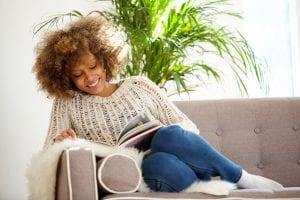 African American woman in a sweater sitting on sofa reading book