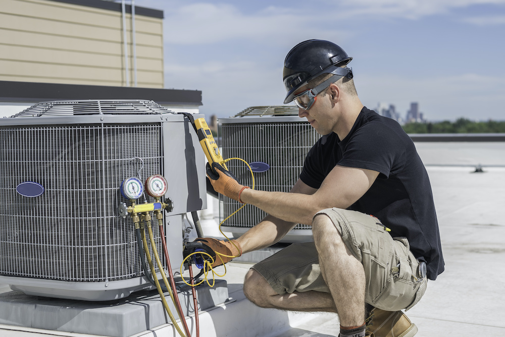 A technician performs AC maintenance on an outside unit.