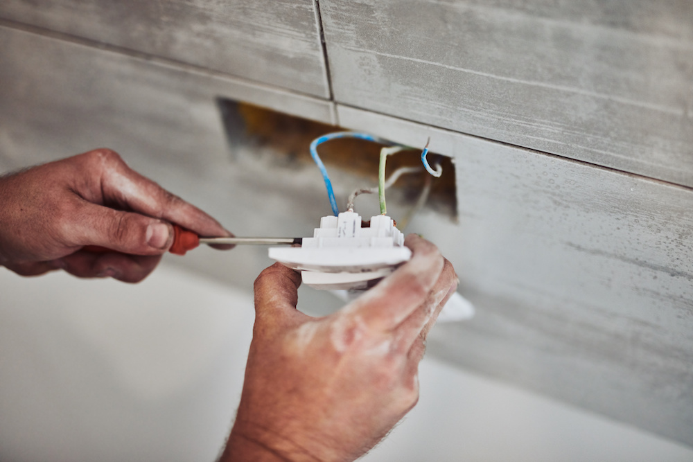 A person's hands are performing electrical repair on an outlet.