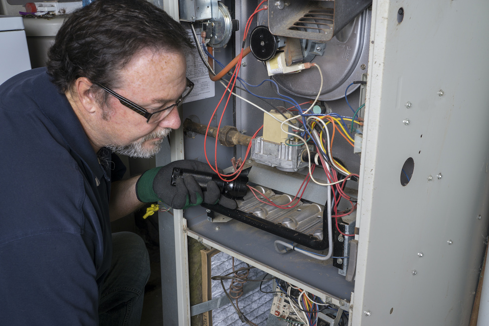 A man looks over a gas furnace with a flashlight while performing heating repair.