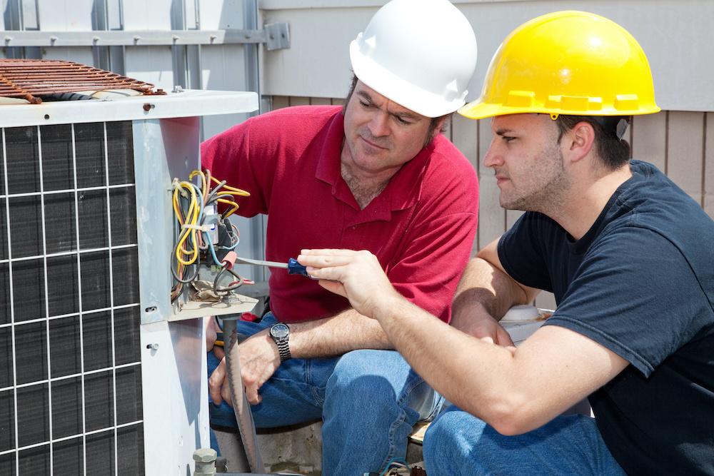 Two technicians perform HVAC maintenance.