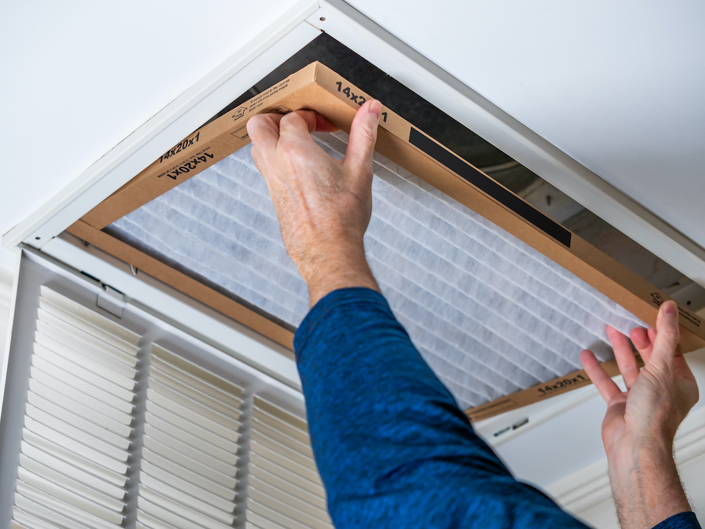 Changing an air filter to improve indoor air quality.