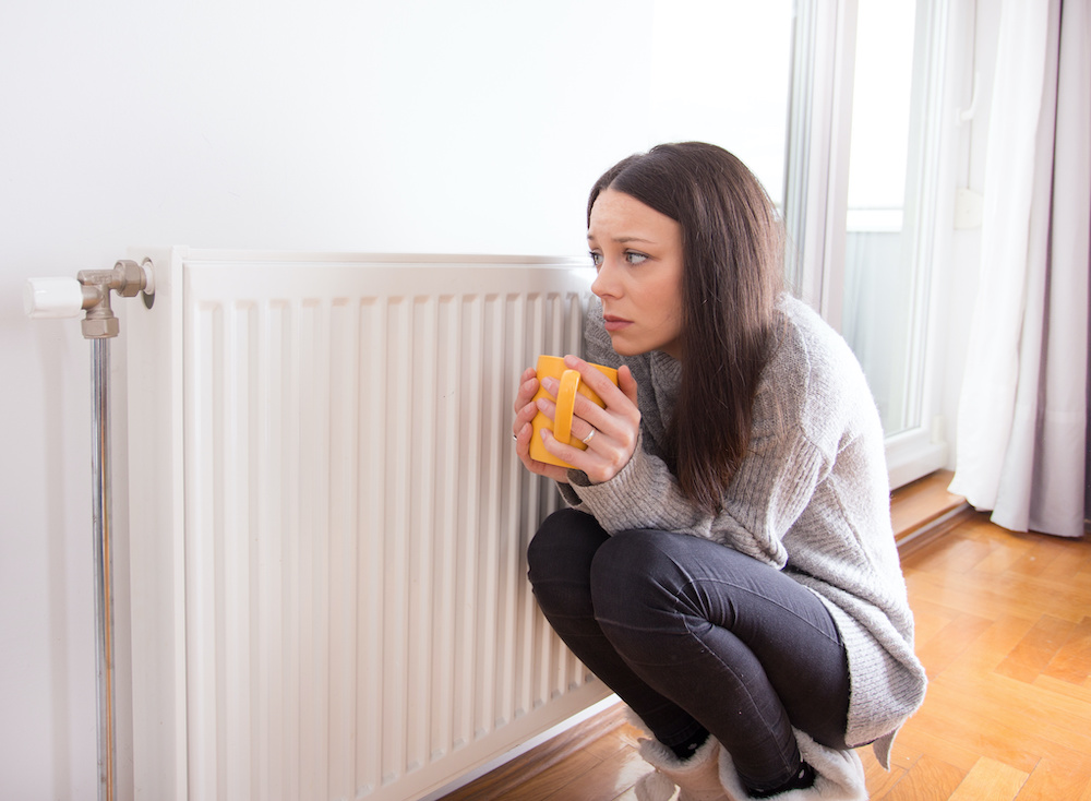 Girl in need of heating repair, cold and cuddled up by heater