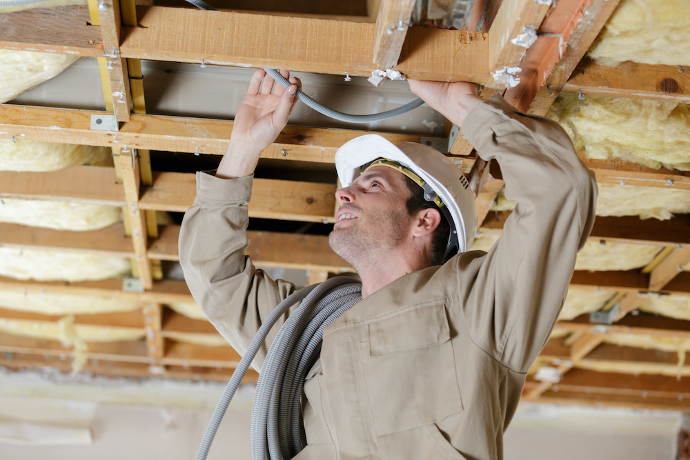 A worker performs some home rewiring in the ceiling.