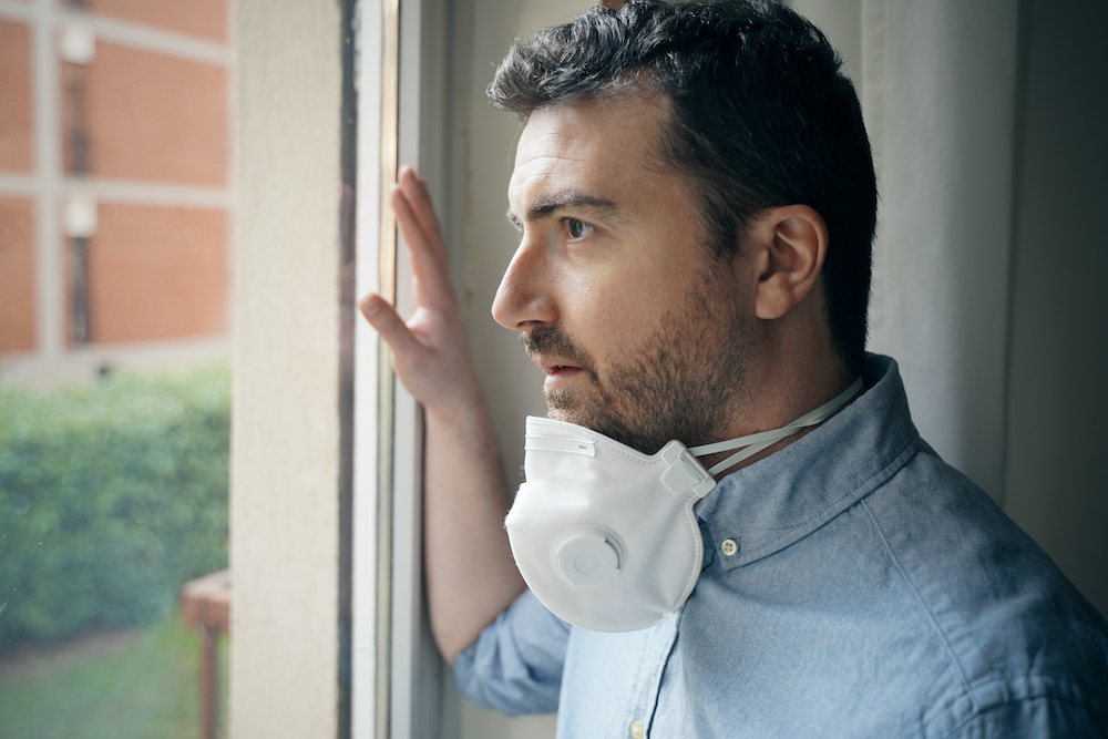 A man wears a mask and looks out his window.