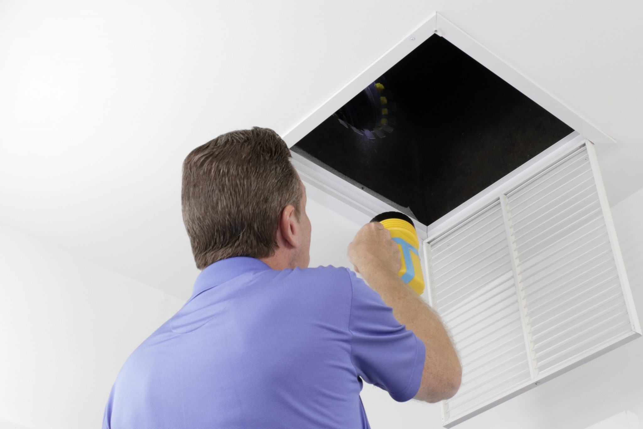 Older male with a yellow flashlight examining HVAC ducts in a large square vent.
