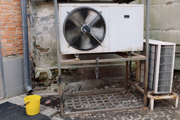 An elevated HVAC unit next to a wall