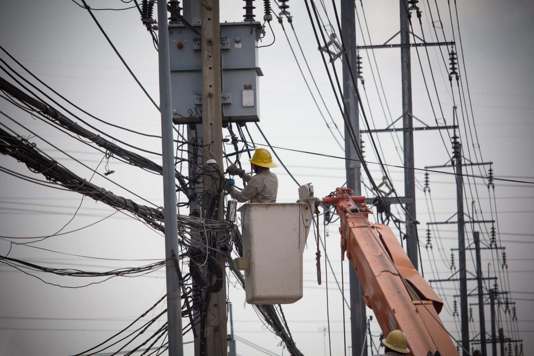 echnician checking fixing broken electric wire on pole. Electricity power utility worker in crane truck bucket fixes high voltage power transmission line.