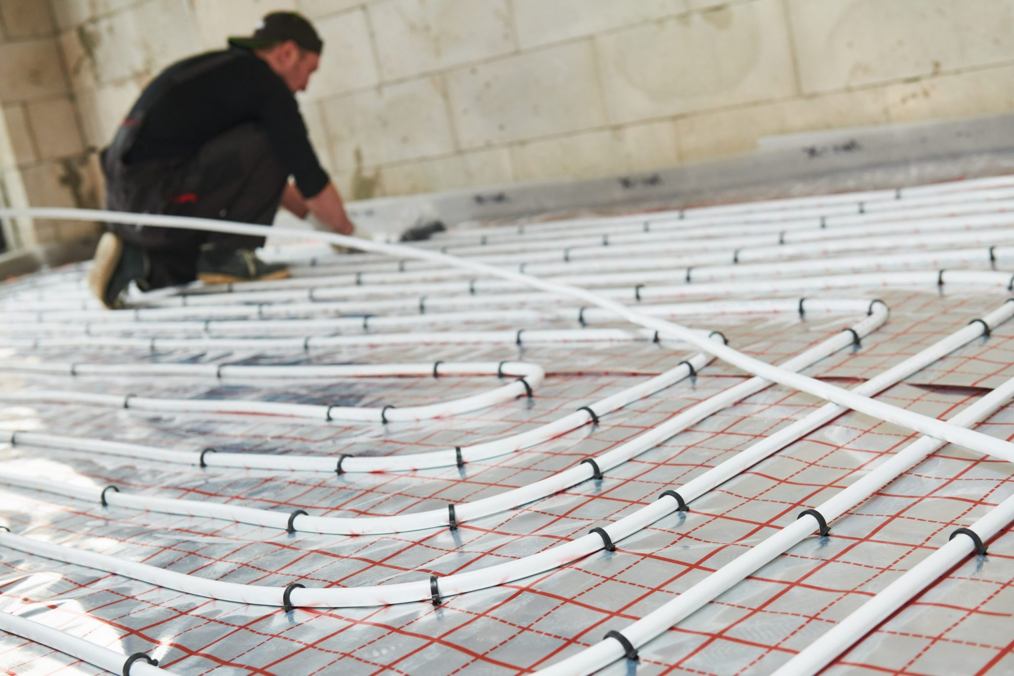 Man installing floor heating system.