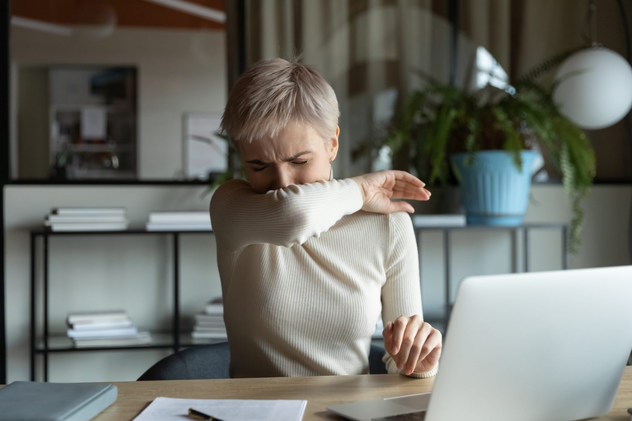 Front view young female manager with short haircut coughing or sneezing in elbow while working on laptop in office room.