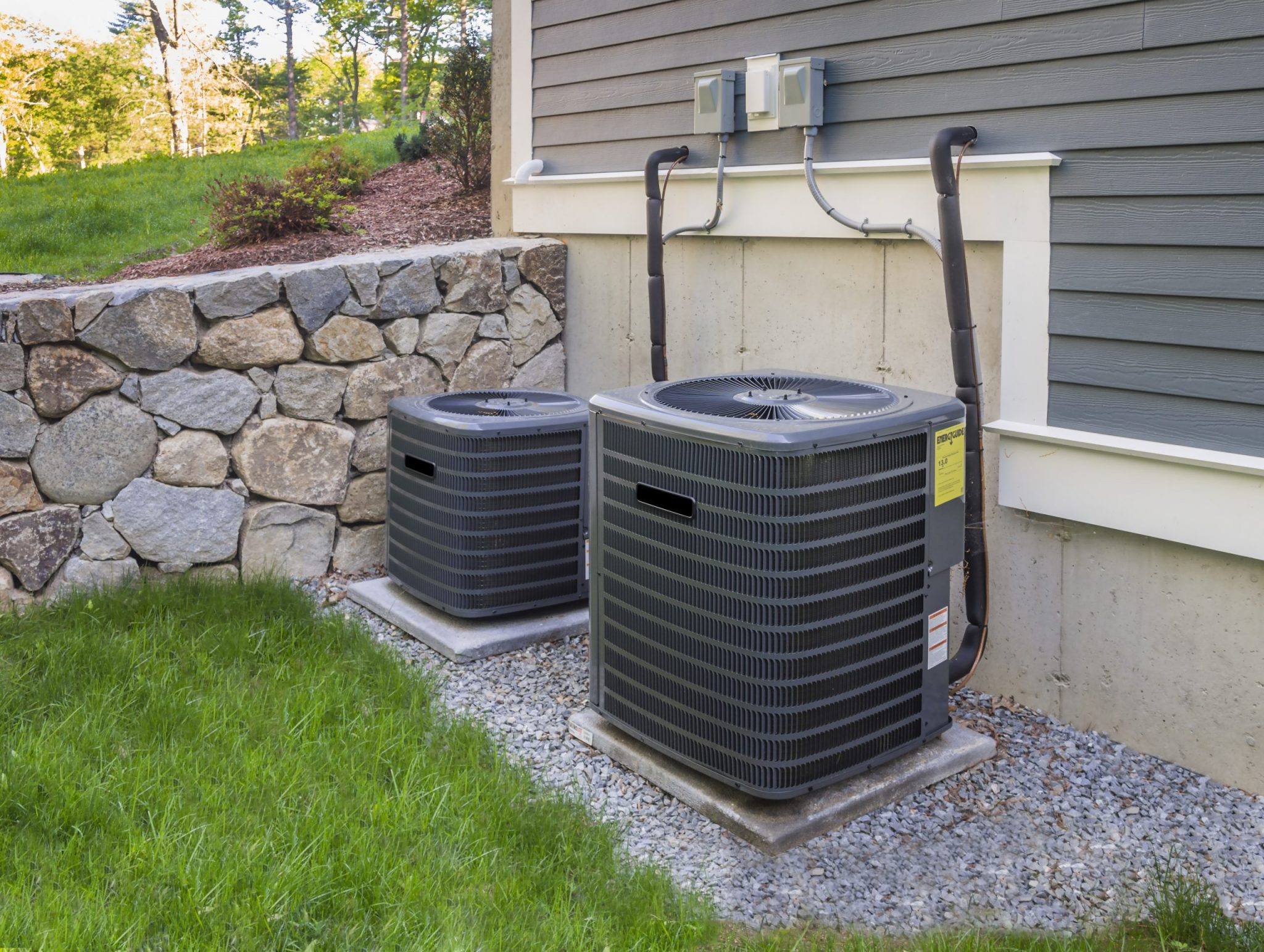 Two HVAC units beside a house in a yard