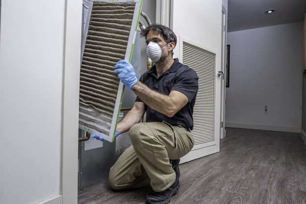 Man with face mask and gloves changing dusty AC filter