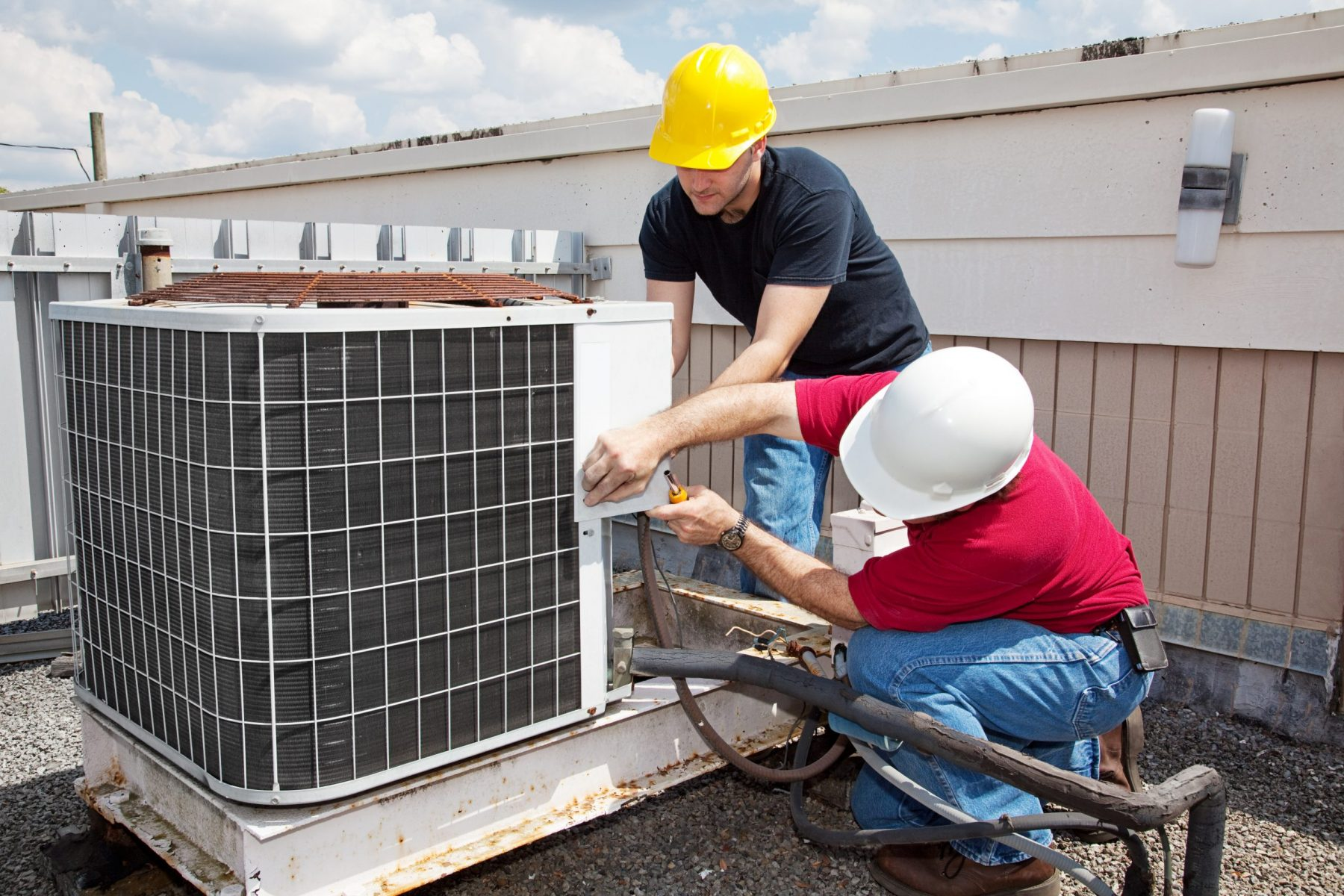 Two workers on the roof of a building working on the HVAC unit