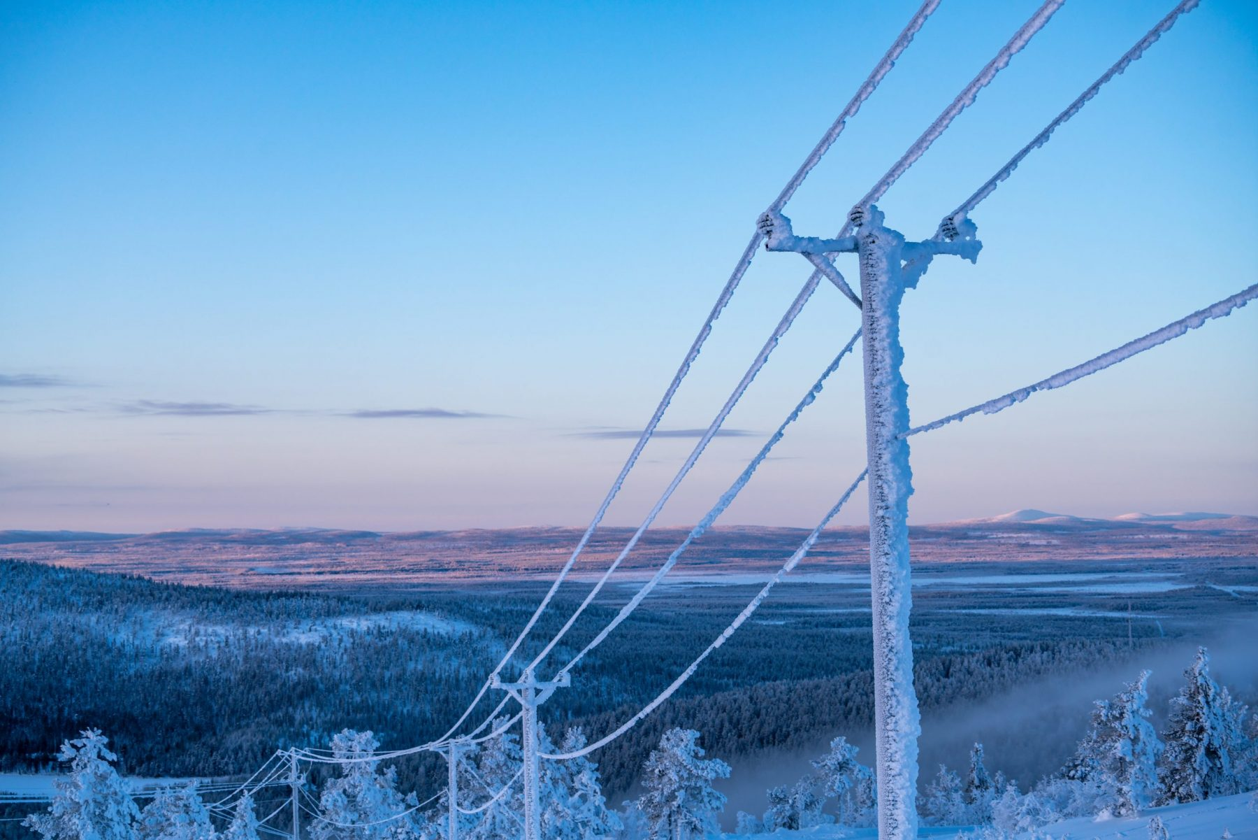 Power lines covered in snow and frost in a wintry background